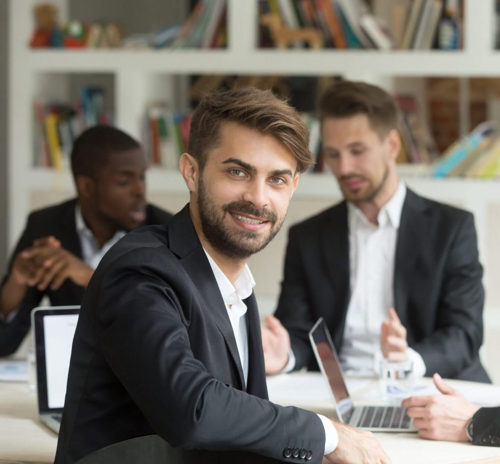Smiling team leader looking at camera on group corporate meeting